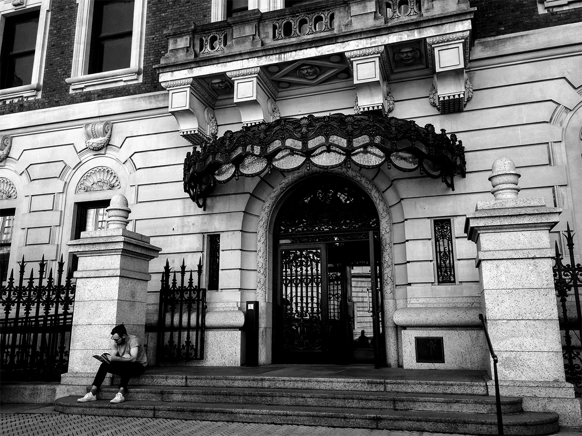 a man sits on the steps to the Cooper Hewitt Museum