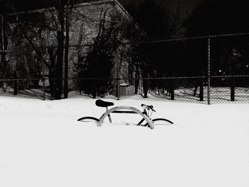 A bicycle sits submerged in heavy snowfall