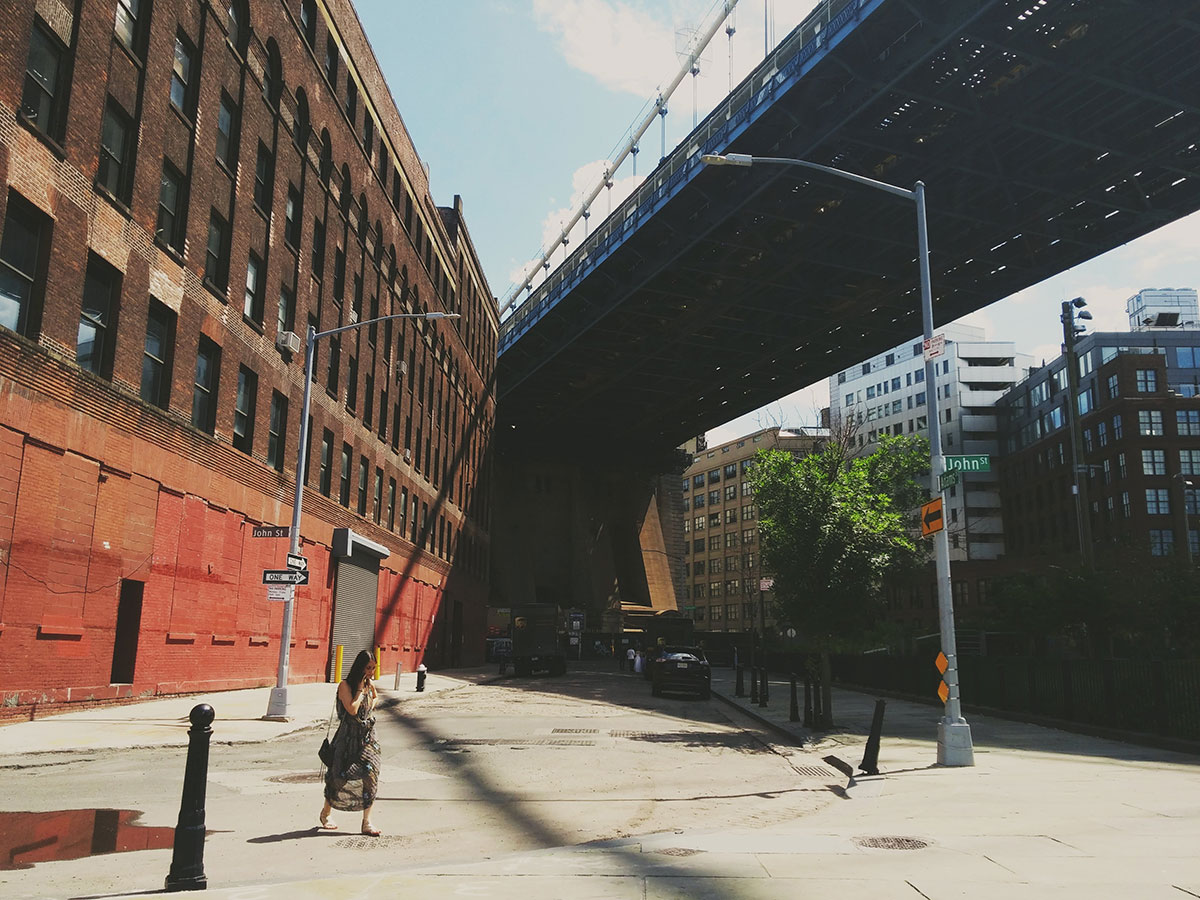 a woman walks under a bridge in DUMBO