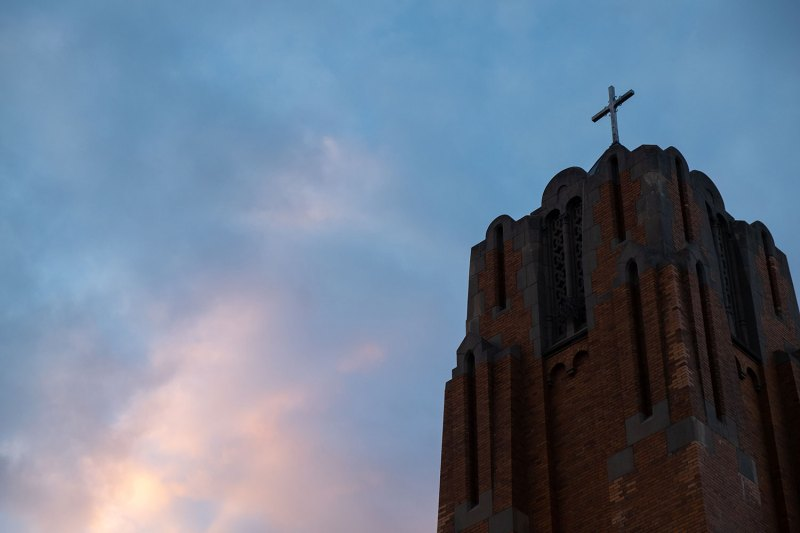 a cross on top of a church spire illuminated by sunset