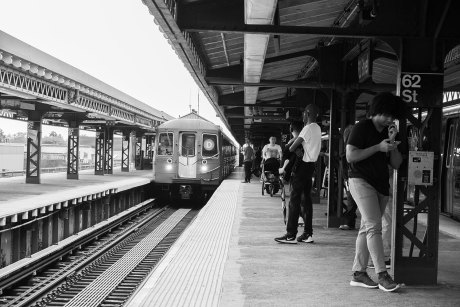 people waiting for a train at 62nd street in brooklyn