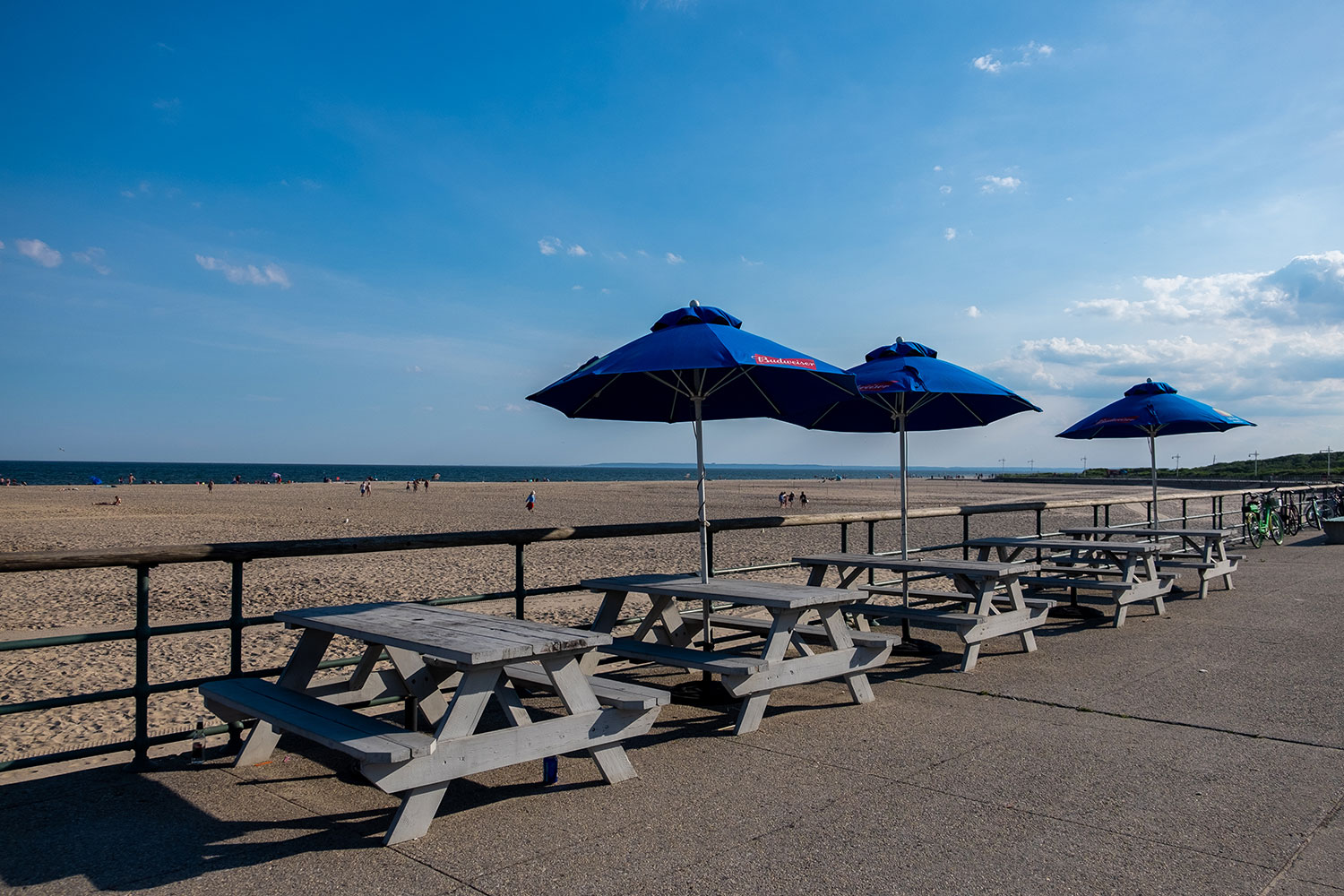 picnic tables lined on the boardwalk at Jacob Riis Beach