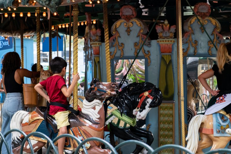 a boy rides a merry go round in Bryant Park