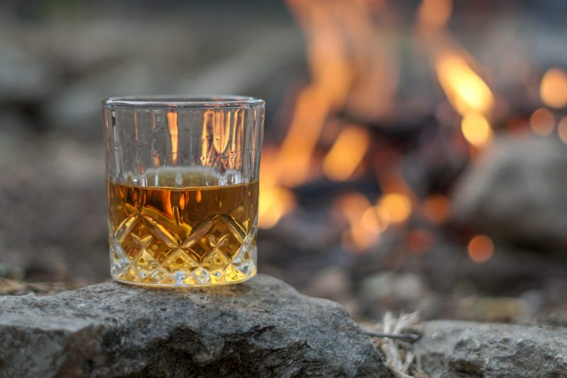 a glass of bourbon balanced on a rock in front of a fire pit