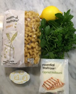 Photo showing a bag of maori pasta, fresh herbs, a lemon, a block of halloumi and a chicken stock pot