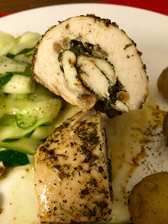 Shot showing the chicken roulade sliced in half with halloumi, basil and pine nuts visible. Plated up with shaved courgette salad and baby new potatoes.