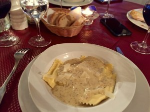 Shot showing ravioli with truffle sauce served with red wine on a beautiful red tablecloth.