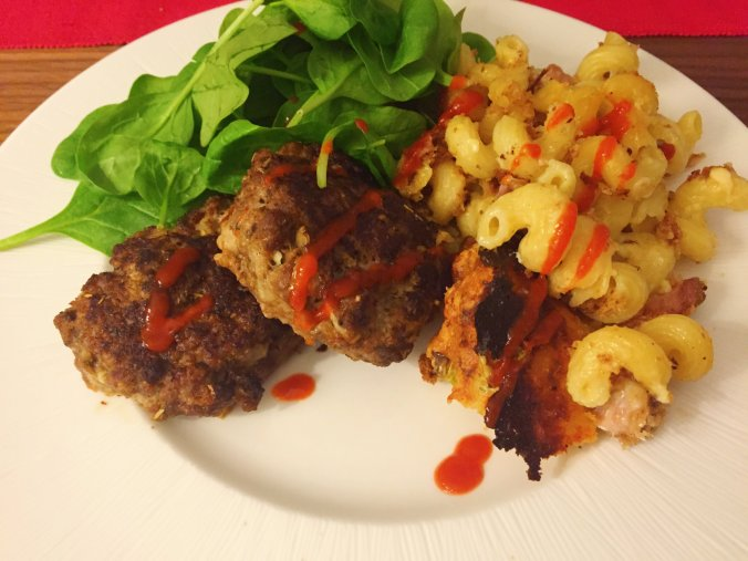 Shot showing the finished dish, served with mac and cheese and salad.