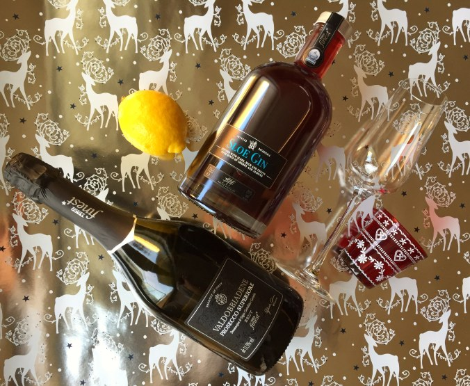Arial shot of prosecco, sloe gin and other ingredients on a festive silver background.