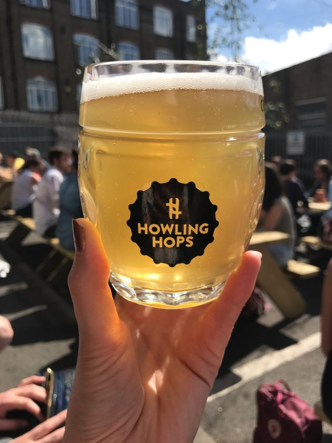 Raising a glass of locally brewed beer to the sun at Howling Hops, Hackney Wick