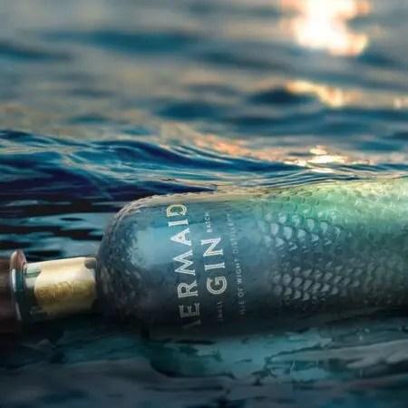 Flaske Mermaid gin, der ligger i havet.