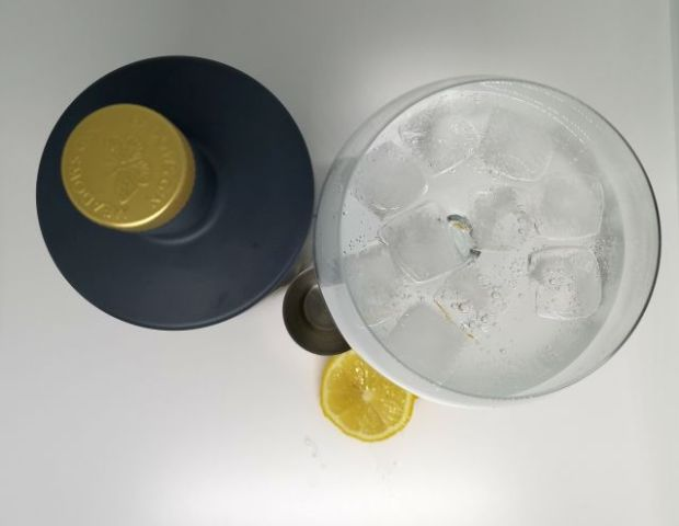 Top down image of a grey bottle with a gold embossed top, next to a silver jigger, slices of lemon and a gin copa glass filled with gin tonic and ice, with a white background.