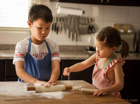 Kids rolling out dough for homemade Chinese noodles