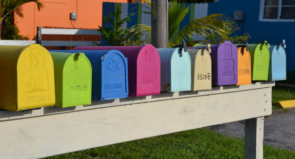 horizontal line of brightly colored mail boxes all in a row on a wood platform
