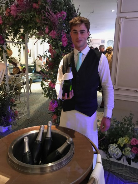 Really hot Fortnum and Mason staff member serving champagne