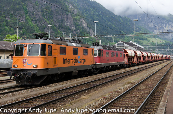 Interregio Cargo branded Re 4/4 II, number 11320 with Re 6/6 11634 sits in Erstfeld station at the head of train number 67167 Huntwangen-Wil to Sigirino formed of Holcim hoppers on the 23rd of May 2013.