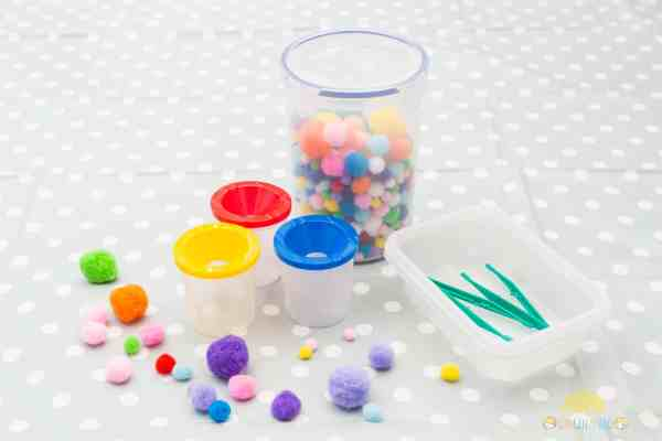 Colourful pompoms, cups and forceps for a toddler or preschooler game by GinGin & Roo