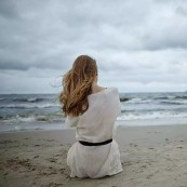 photo of young lonely depressed woman on cold windy beach