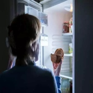woman opening refrigerator to eat