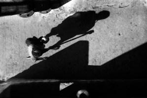 A beggar walking along the streets of Yadagiriguda Temple in Andhra Pradesh. 1994. Title: Shortening Shadows of a Saint (series)