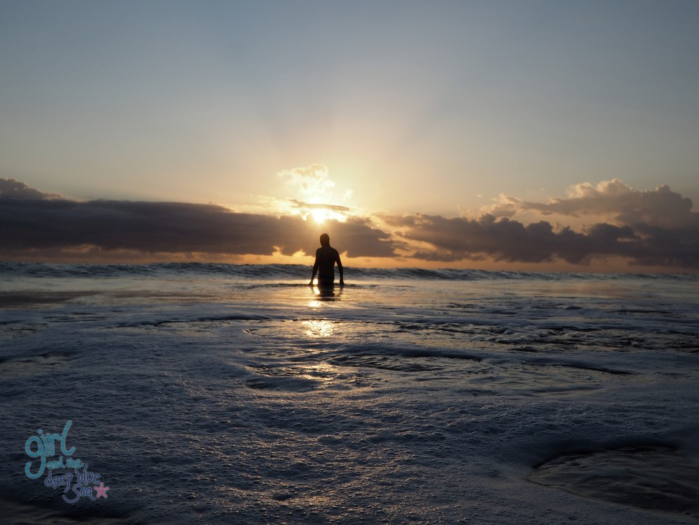 person in ocean at sunrise Burleigh