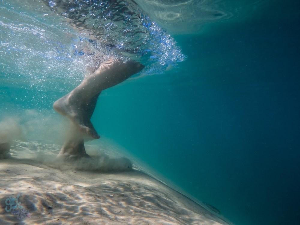 person running underwater on sand