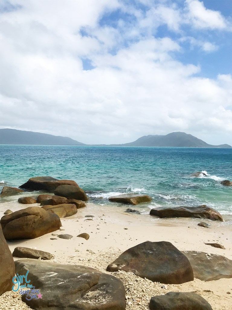 coral beach with large brown rocks, white sand, blue waters and mountains in background in tropical North Queensland