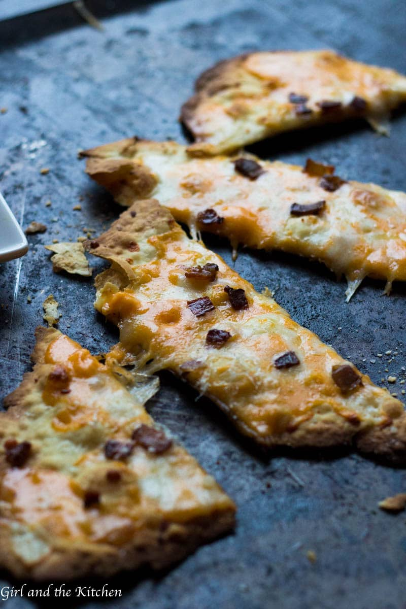 Prepare for the crispiest and easiest flatbread ever! This cheesy bacon flatbread comes together in one bowl without the need for any kneading! In no time at all, you will have a crispy flatbread loaded with the most delicious of goodies!