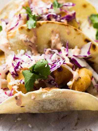 These delicious beer battered crispy fish tacos are a new twist on a Baja classic! Dipped in a spicy beer batter and topped with a crunch and fresh slaw, these fish tacos will be the new standard to any summer party!