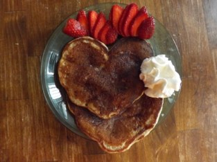 heart shaped chocolate chip pancakes with strawberries and whipped cream.