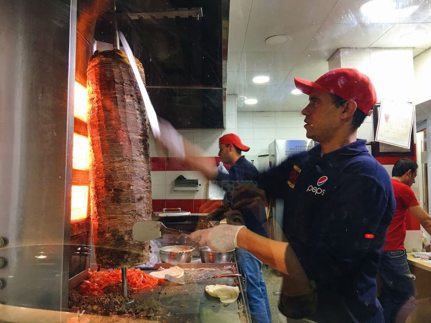 Shaving meat off the vertical spit for Shawarma wrap