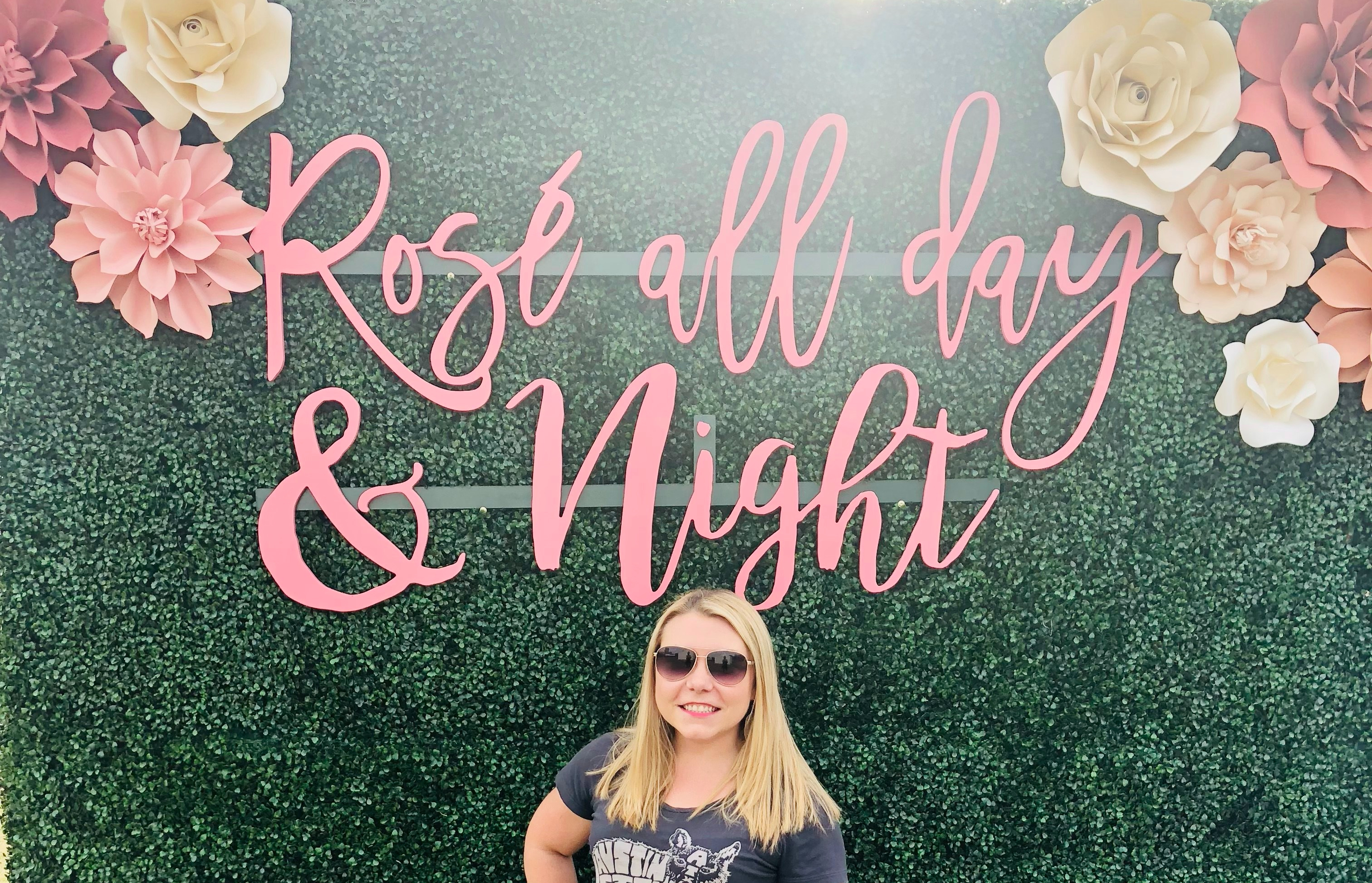 Jenn standing in front of Rosé All Day & Night greenery wall