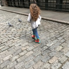 Chasing pigeons on the cobblestone of Stone Street