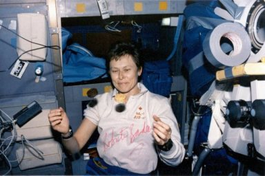 Dr. Roberta Bondar eating Canadian Girl Guide cookies in space!