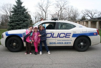 Chloe, Marci and Kate pose in front of the cruiser