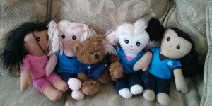 Making Guiding friends: A Girl Guiding UK bear snuggles up with some Sparks dolls.