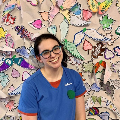 Alyssa, a Ranger from Brooklyn, Ontario in blue Girl Guides uniform in front of an art wall