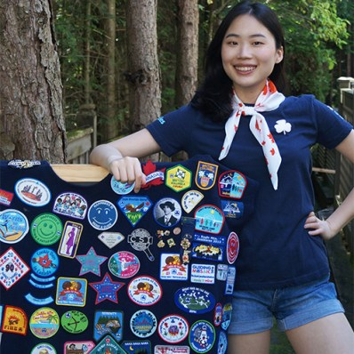 Ella, a Ranger from Port Moody, British Columbia in a blue Girl Guides uniform standing next to a crest poncho