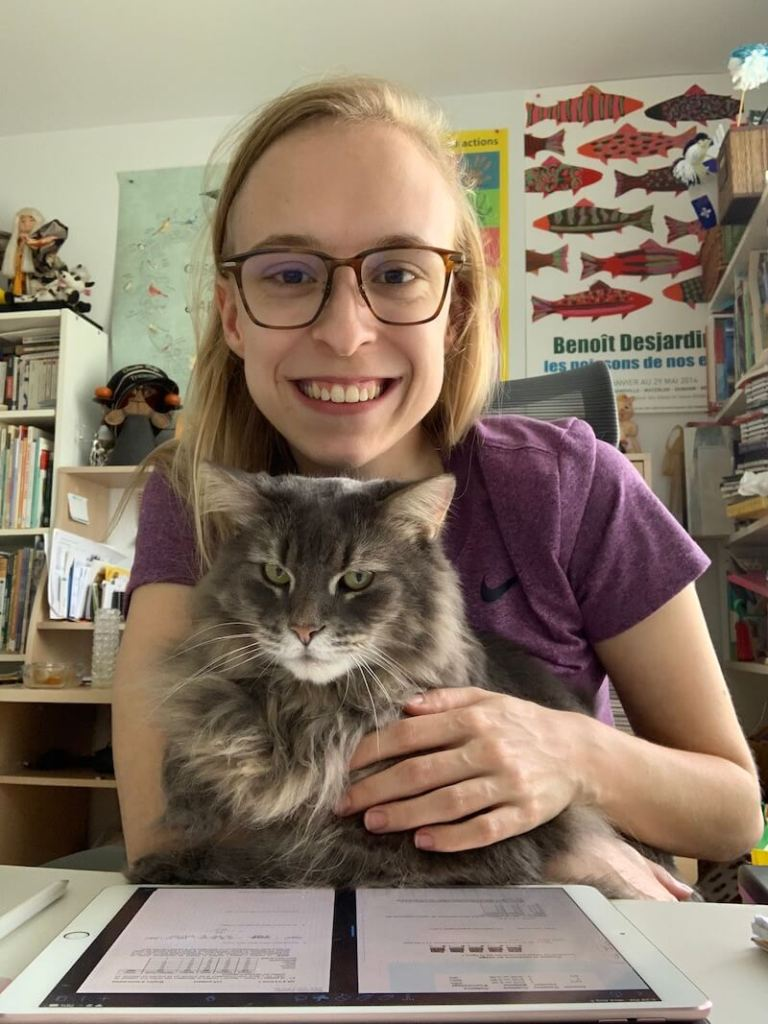 Marie and her cat Minou sitting on her at her desk