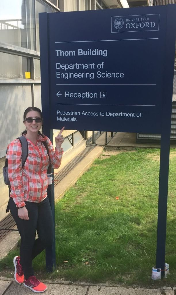 Caroline Lecours in front of a sign for University of Oxford where she did a research stay for her Ph.D. studying concussions in football.