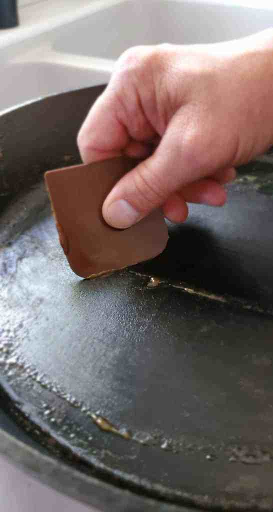 a picture of a hand holding a scraper and removing stuck on food debris from cast iron