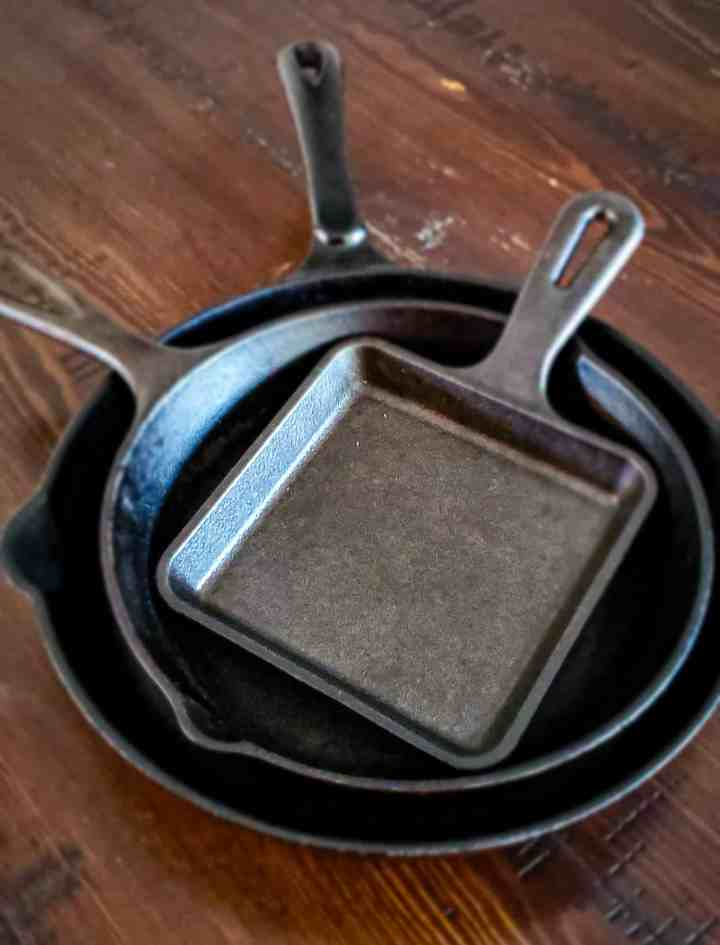 a stack of cast iron pans on top of a dark wood table