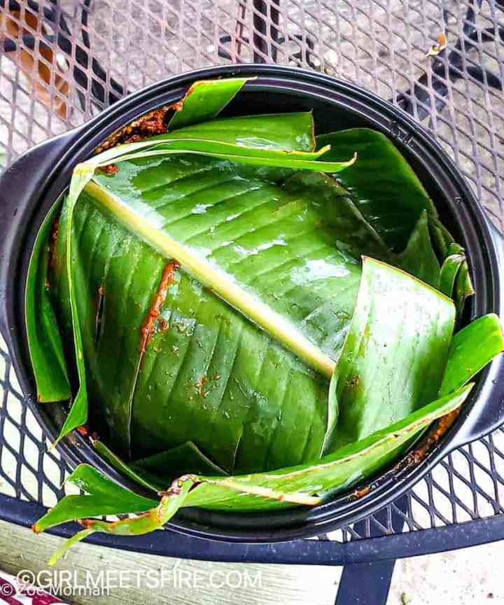 Pork fully covered with banana leaves inside of the crock