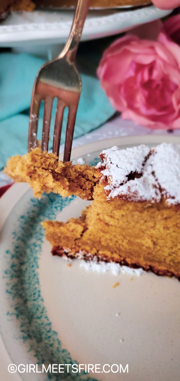 A slice of cake with a fork pulling a bite out of it.