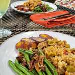 two plates of arroz con pillow served with sautéed green beens and pan fried ripe plantains