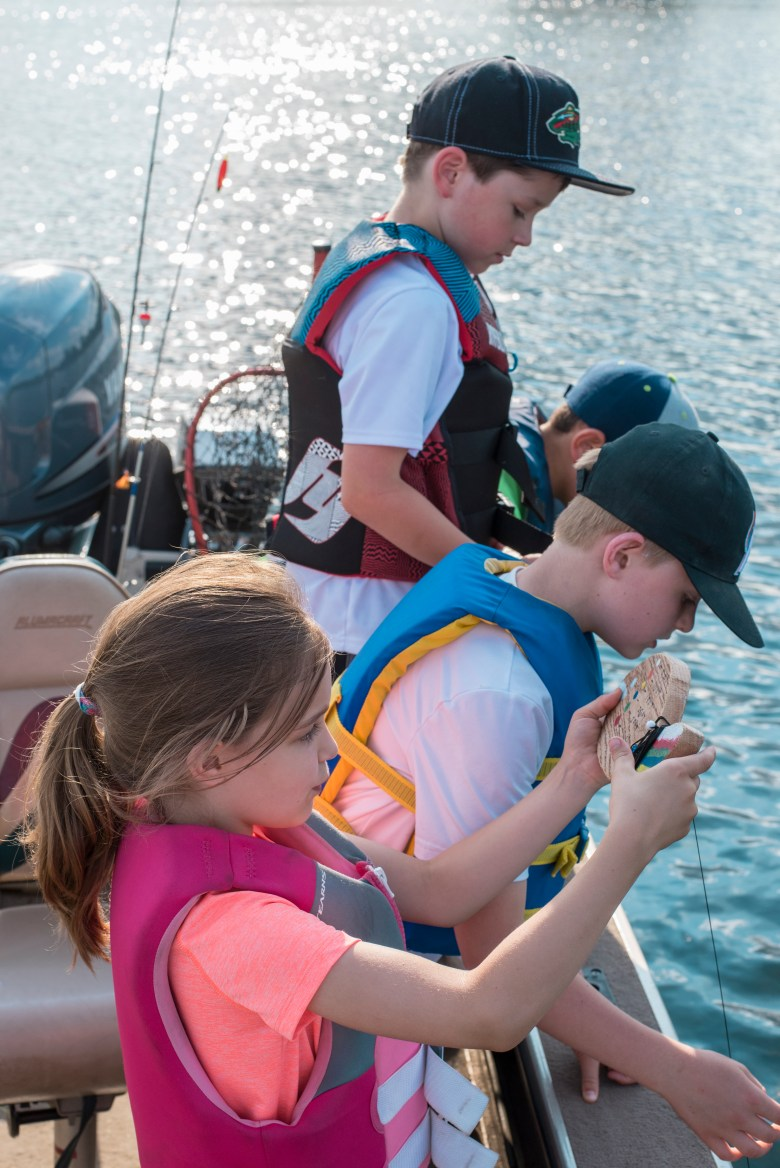 Kids learning how to measure the depth of the lake