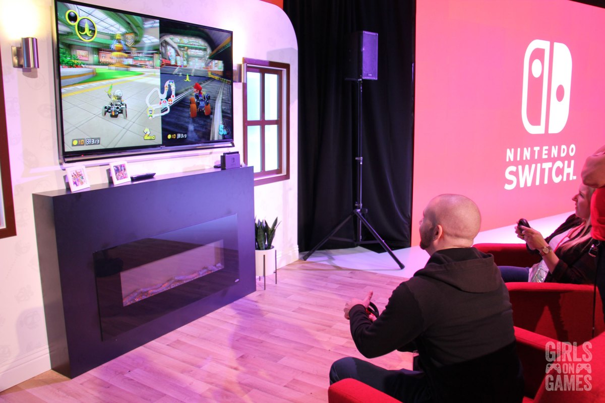 Attendees playing Mario Kart 8 Deluxe in a living room setup at the Nintendo Switch event in Toronto. Photo: Leah Jewer / Girls on Games