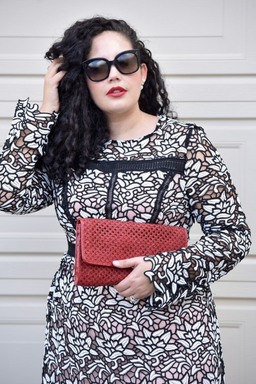Girl With Curves blogger Tanesha Awasthi wears a lace midi dress and red clutch.
