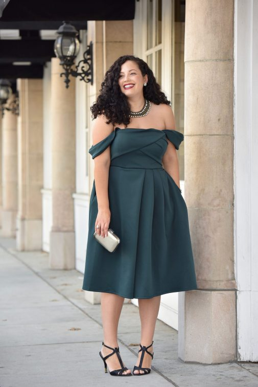 Girl With Curves blogger Tanesha Awasthi wears an emerald off-shoulder dress, silver box clutch and t-strap heels in downtown San Jose, CA.