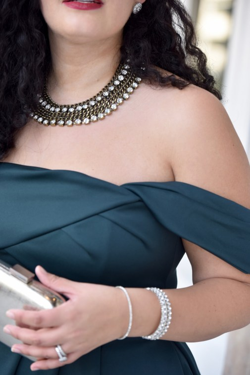 Girl With Curves blogger Tanesha Awasthi wears an emerald off-shoulder dress, silver box clutch and rhinestone bangles.